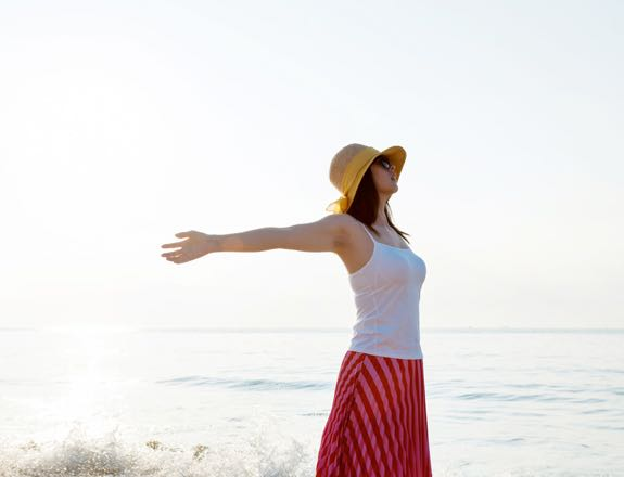 Woman with arms open on the beach